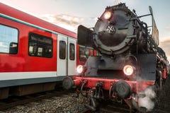 Vieux train de vapeur et train électrique moderne dans une course Photos stock