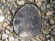 Vieux tronçon d'arbre avec la pierre de caillou, passage couvert de décoration dans le jardin avec les matériaux naturels photos libres de droits