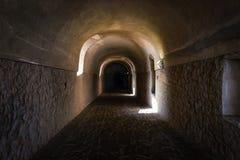 Vieux tunnel de pierre et béton avec la lumière du soleil de fenêtres dans le château photos stock