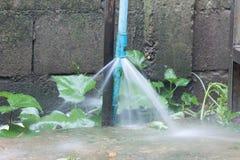 Vieux tuyau rouillé de PVC avec de l'eau la fuite et pulvérisant  Image stock