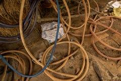 Vieux tuyaux de cru sur la terre concrète sale - foin, bois et Rusty Knife dans la cage de poulet malpropre - le Vietnam rural photographie stock libre de droits