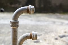 Vieux tuyaux rouillés avec des robinets, des garnitures, des valves, des prises et l'enroulement sur une rue de ville photo stock