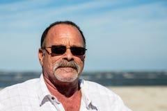 Vieux type dans la chemise blanche avec des lunettes de soleil Photographie stock libre de droits