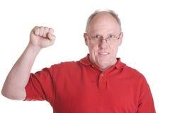 Vieux type dans la chemise rouge avec le poing en air Photographie stock