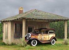 Vieux véhicule de cru par une petite construction Photographie stock