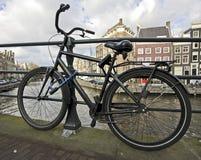 Vieux vélo hollandais enchaîné contre une passerelle Photos libres de droits