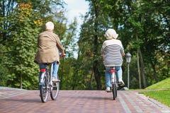 Vieux vélos d'équitation de ménages mariés en parc images stock