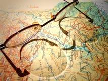Vieux verres ronds de vintage s'étendant sur une carte de l'Europe avec l'ombre dure photos stock