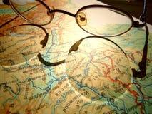 Vieux verres ronds de vintage s'étendant sur une carte de l'Europe avec l'ombre dure image libre de droits