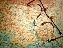Vieux verres ronds de vintage s'étendant sur une carte de l'Europe avec l'ombre dure image stock