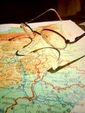 Vieux verres ronds de vintage s'étendant sur une carte de l'Europe avec l'ombre dure images stock