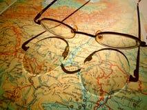 Vieux verres ronds de vintage s'étendant sur une carte de l'Europe avec l'ombre dure Photographie stock