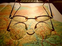 Vieux verres ronds de vintage s'étendant sur une carte de l'Europe avec l'ombre dure images libres de droits
