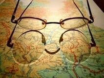 Vieux verres ronds de vintage s'étendant sur une carte de l'Europe avec l'ombre dure photos libres de droits