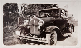 Vieux véhicule du modèle T d'entraînement de jeune homme de photographie de cru Photographie stock