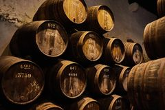 Vieux a vieilli les barils en bois traditionnels avec du vin dans une chambre forte alignée dans la cave fraîche et foncée en Ita image stock