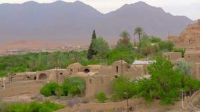 Vieux village d'adobe situé dans une oasis au coucher du soleil banque de vidéos