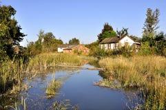Vieux village par l'étang Photographie stock libre de droits