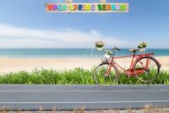 Vieux vintage rouge de bicyclette sur la route avec la fleur dans le panier, bouquet f Images libres de droits