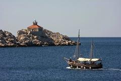 Vieux voilier en bois et le phare Photographie stock libre de droits
