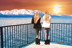 The View. Two young women standing at the edge of a pier, over a lake,  observing a beautiful sunset over snowcapped mountains Royalty Free Stock Photos