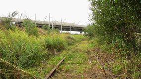 View of an abandoned old railways in summer windy day.Motorway on a background. stock video footage