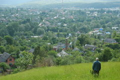 View from above. Elderly man is looking from a hill on the small town situated in a valley . Khadyzhensk. Krasonodar Territory. Russia Royalty Free Stock Photography