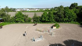 View from above, aerial video shooting, training sand field, playground, riders, jockeys ride horses, perform various. Exercises with horses, next to barriers stock video footage