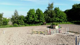 View from above, aerial video shooting, training sand field, playground, riders, jockeys ride horses, perform various. Exercises with horses, next to barriers stock footage