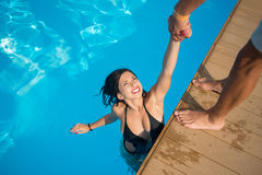 View from above of attractive girl in the swimming pool holding a man`s hand trying to get out at resort Royalty Free Stock Photo