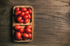 View from above of baby tomato on wood Stock Images