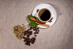 View from above of beans with hot coffee inside. View from above on assorted types of different java beans and herbs beside steaming hot teacup full of coffee Royalty Free Stock Photography
