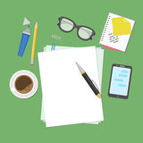 View from above of blank sheets of paper, pen, pencil, marker, smart phone, a notebook, stickers, glasses, coffee cup. Royalty Free Stock Photos