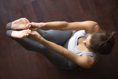 View from above. Both Big Toe Yoga Pose. Beautiful young model working out at home, doing yoga exercise on floor, siting in Both Big Toe Pose, Paripurna Navasana royalty free stock photography