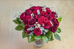 View on above on a bouquet of red roses with green leaves in a g. Lass vase on a wooden table stock photo