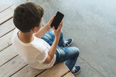 View from above. Boy in white T-shirt and sunglasses sitting indoor and uses smartphone. Teenager plays computer games Royalty Free Stock Image