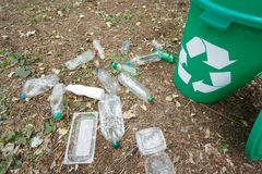 Green recycling bin next to plastic trash on a ground background. Containers for rubbish recycling. Environment, ecology Stock Photo