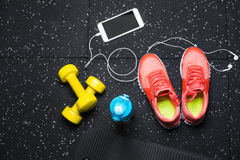 A top view of pink trainers, bottle for water, phone and small dumbells on a black background. Sports accessories. A view from above of bright pink training Royalty Free Stock Images