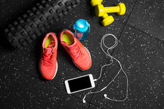 A top view of pink trainers, bottle for water, phone and small dumbells on a black background. Sports accessories. A view from above of bright pink training Stock Photos