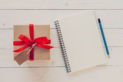 View above brown gift box and notebook with tag on wood backgrou Royalty Free Stock Photography
