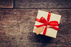 View above brown gift box and red ribbon with tag on wood background with space. stock photo