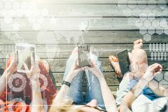 View from above.Close-up of smartphones in hands of group of people sitting outside. stock illustration