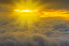 View above the clouds and yellow light beams Stock Photo