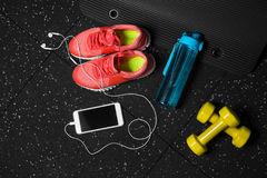 A top view of trainers, sports bottle, phone and dumbbells on a black background. Sports accessories. Copy space. A view from above of colorful training shoes Royalty Free Stock Image
