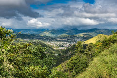 View from above down into a Puerto Rican town in the valley. View of rural Puerto Rican town in the valley at the base of the mountains with cloudy stormy sky Royalty Free Stock Photography