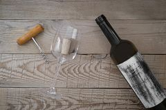View from above of an empty wine bottle, a corkscrew and a cork. In empty wine glass on a wooden table Stock Image