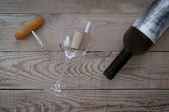View from above of an empty wine bottle, a corkscrew and a cork. In empty wine glass on a wooden table Stock Photo