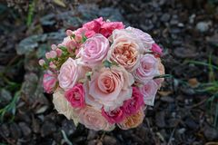 View from above of an exquisite bridal round bouquet featuring roses in different hues of pink, berries and silky peonies Royalty Free Stock Photos