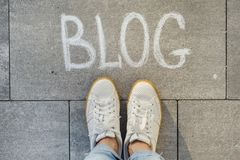 View from above, female feet with text blog written on grey sidewalk royalty free stock photography