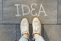 View from above, female feet with text idea written on grey sidewalk stock image